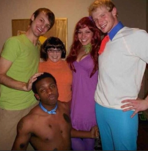 A young black man poses with white friends in a Scooby Doo costume and sparks outrage.