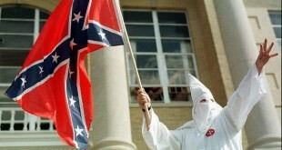 A member of the American Knights of the Ku Klux Klan waves the Confederate flag during a klan rally on the steps of the Warrick County courthouse in Boonville, Ind., on Saturday, Oct. 17, 1998. (AP Photo/Evansville Press, Jonna Spelbring)