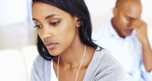 Closeup of sad young woman in living room with man after an argument
