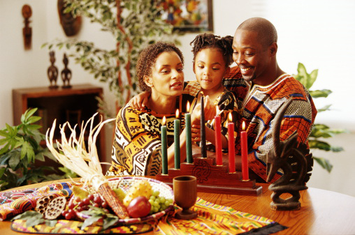 Parents and daughter (4-6) lighting Kwanzaa candles