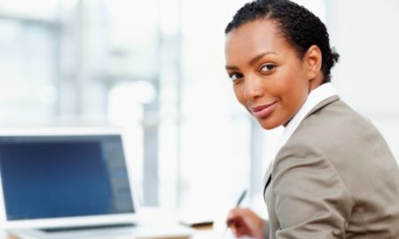 Portrait of a charming African American business woman using laptop